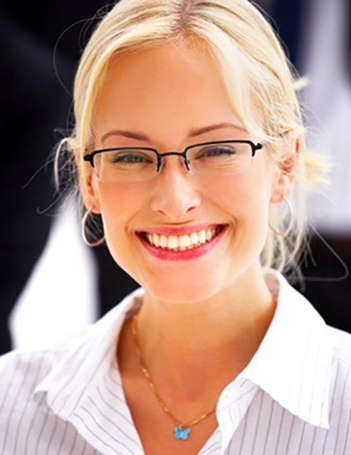 Selbstbewusste Frau mit strahlend weißen Zähnen nach dem Bleaching