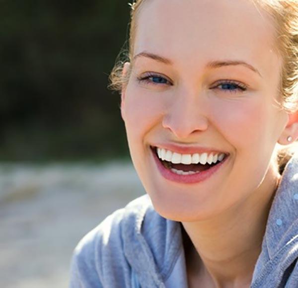 Lachende junge Frau mit Implantaten