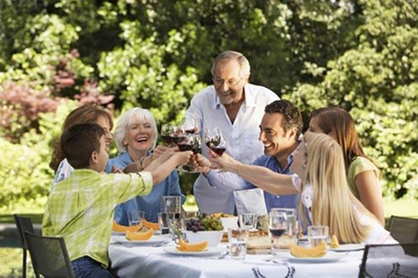 Gruppe aus Personen verschiedener Altersgruppen sitzen lachend im Garten mit Implantaten