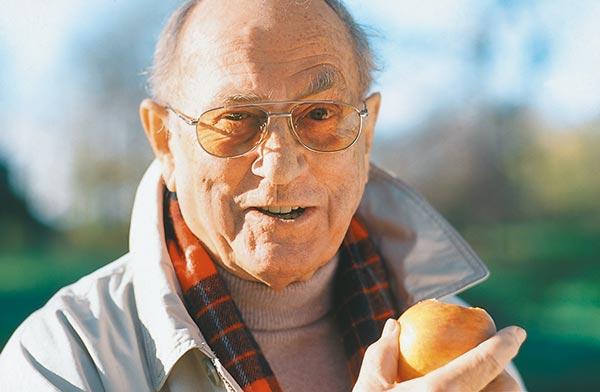 Älterer Mann mit Implantat freut sich einen Apfel essen zu können