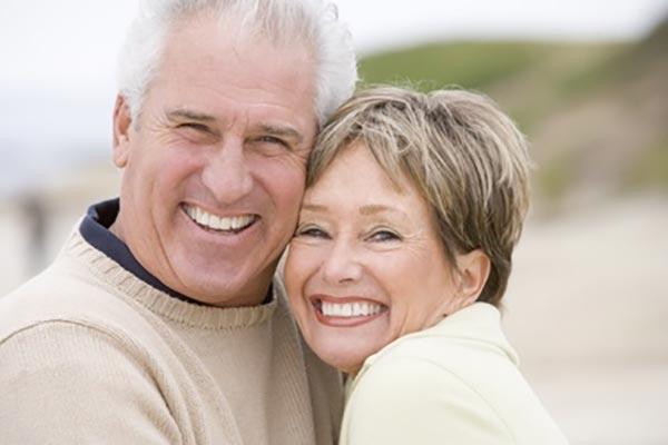 Älteres sorgenlos lachendes Paar mit Implantaten