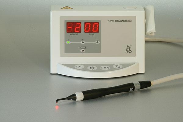 DIAGNOdent bestehend aus einer weißen Konsole und einem schwarzen Laserkopf wird zur Diagnose von Karies verwendet.
