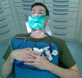 Patient hält eine Sauerstofflasche in der Hand, welche an einer Sauerstoffnasenbrille angebracht ist. Zudem trägt er einen Kofferdam und einen Schwimmbrille zum Schutz.
