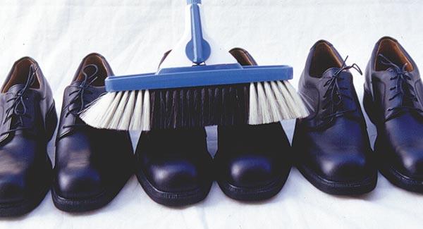 Drei nebeneinander stehende Paar Schuhe werden mit einem Besen gebürstet wodurch keiner komplett sauber werden kann