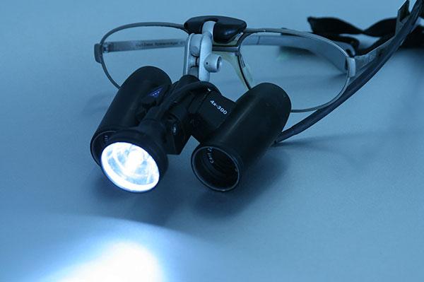 Die Lupenbrille sieht einer Brille ähnlich, an die ein Fernglas mit Taschenlampe montiert wurde